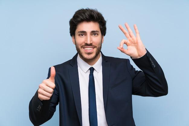 Uomo d'affari sopra la parete blu isolata che mostra segno e pollice giusti sul gesto