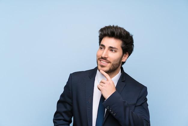 Uomo d'affari sopra la parete blu isolata che pensa un'idea mentre osservando in su