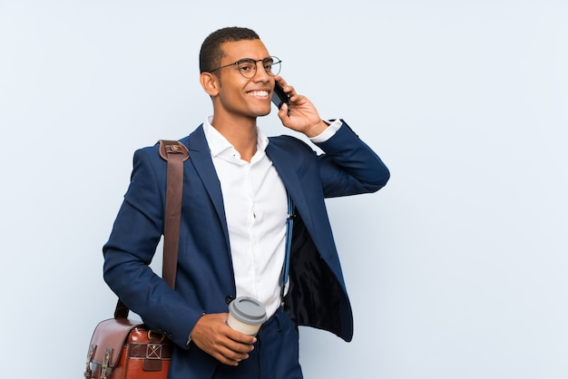 Uomo d'affari sopra la parete blu isolata
