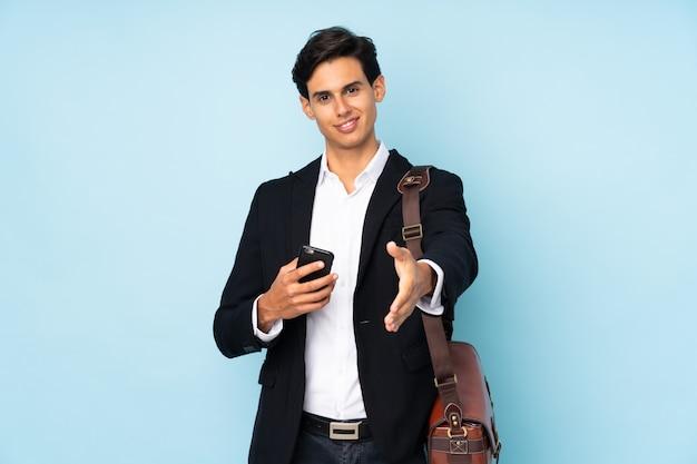 Uomo d'affari sopra la stretta di mano blu isolata della parete dopo il buon affare