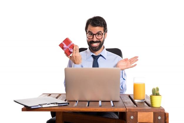 Uomo d'affari sorpreso nel suo ufficio con regalo
