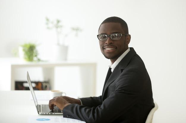 Uomo d'affari sorridente afroamericano in vestito e vetri che esaminano macchina fotografica