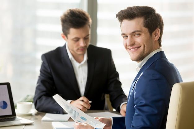Uomo d'affari sorridente, analista finanziario o agente di borsa che guarda a