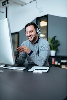 Uomo d'affari sorridente casuale con la cuffia avricolare sul lavoro in ufficio moderno. copia spazio