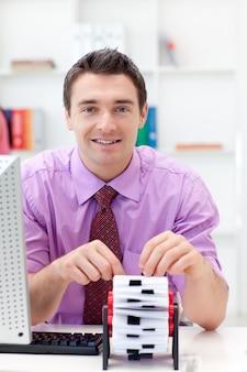 Uomo d'affari sorridente che consulta il suo titolare del biglietto da visita