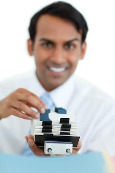 Uomo d'affari sorridente che consulta un titolare del biglietto da visita