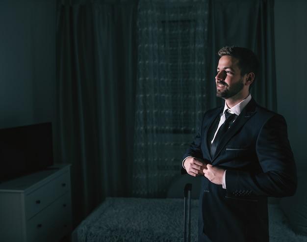 Uomo d'affari sorridente che lega giacca e in piedi nella stanza buia e si prepara per il viaggio d'affari.