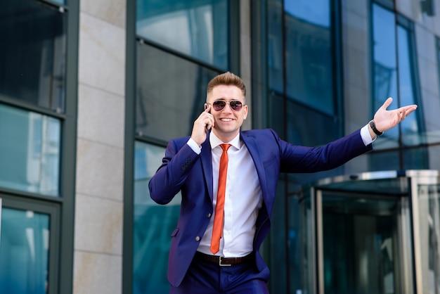 Uomo d'affari sorridente che parla sul telefono e sul saluto.