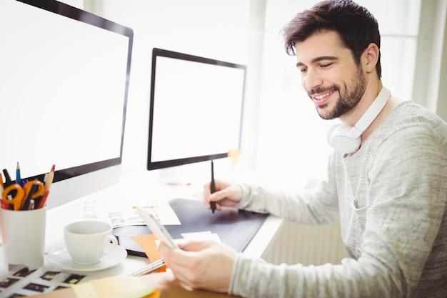 Uomo d'affari sorridente che per mezzo della tavola dei grafici allo scrittorio