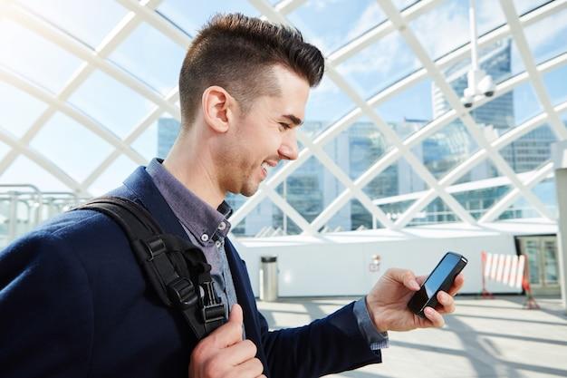 Uomo d'affari sorridente con borsa e telefono cellulare