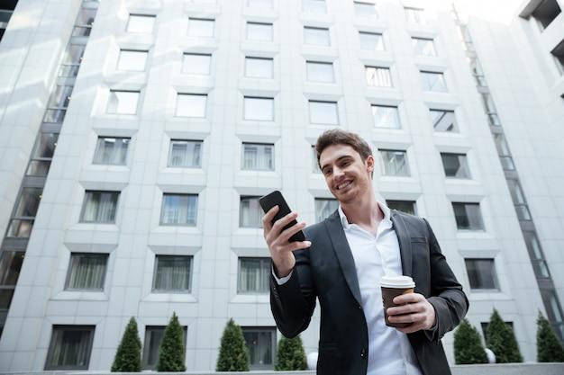 Uomo d'affari sorridente con caffè facendo uso dello smartphone nel centro di affari
