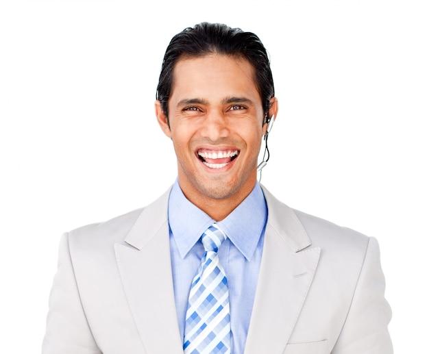 Uomo d'affari sorridente con la cuffia avricolare contro contro