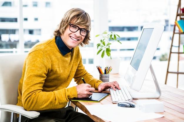 Uomo d'affari sorridente dei pantaloni a vita bassa facendo uso della grafica della compressa nel suo ufficio