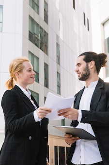 Uomo d'affari sorridente e lavoro di ufficio della tenuta della donna di affari in mani a all'aperto
