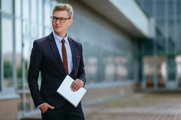 Uomo d'affari sorridente felice con la compressa digitale. concetto di tecnologia moderna