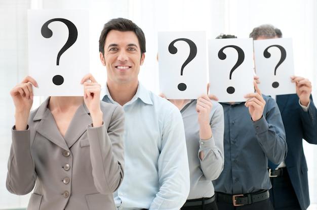 Uomo d'affari sorridente felice in piedi fuori dalla folla con altre persone che nascondono il viso dietro un segno di punto interrogativo.