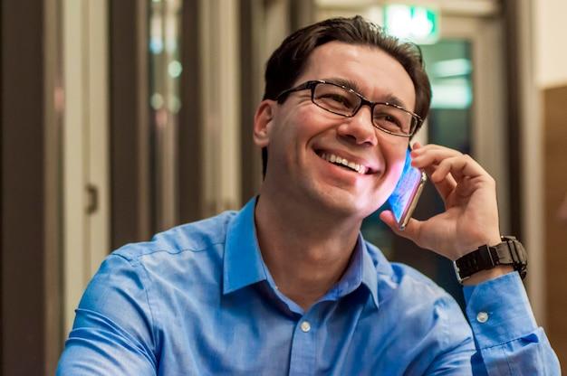 Uomo d'affari sorridente parlando al caffè. uomo d'affari felice utilizzando un telefono cellulare. affari, vendita di auto, persone e tecnologia concetto - felice imprenditore texting su smartphone