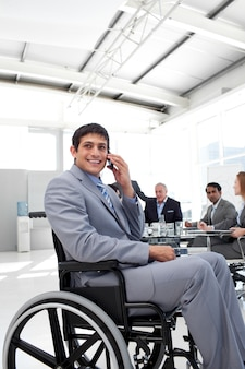 Uomo d'affari sorridente sul telefono che si siede in una sedia a rotelle