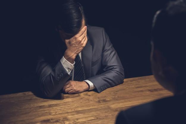 Uomo d'affari sospetto che mostra rimpianto nella stanza scura di interrogatorio