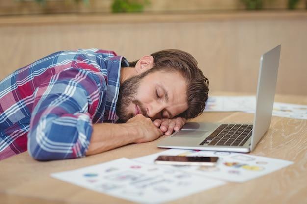 Uomo d'affari stanco che dorme sullo scrittorio mentre lavorando