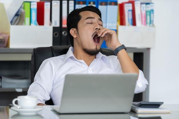 Uomo d'affari stanco che per mezzo del computer portatile e sbadigliando
