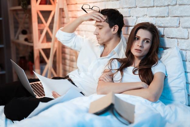Uomo d'affari stanco che si siede a letto lavorando al computer portatile