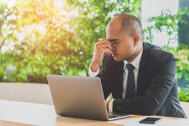 Uomo d'affari stanco stropicciandosi gli occhi. concetto di sindrome di office.