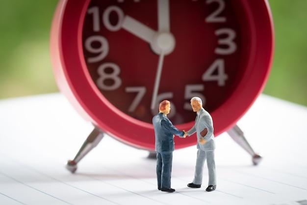 Uomo d'affari stringe la mano in piedi davanti a un orologio rosso.