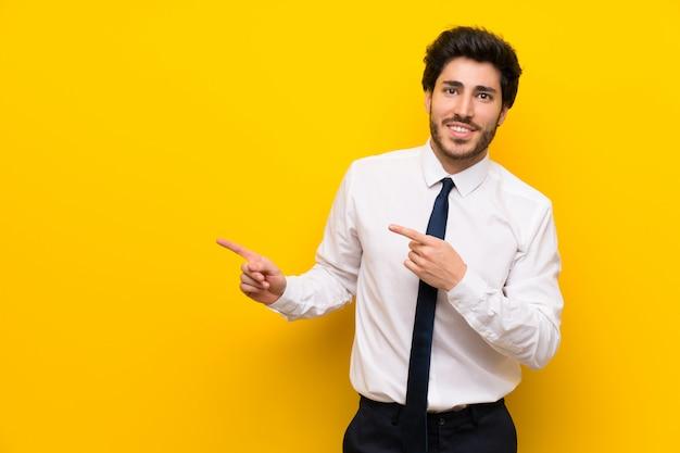 Uomo d'affari sul dito indicante giallo isolato al lato