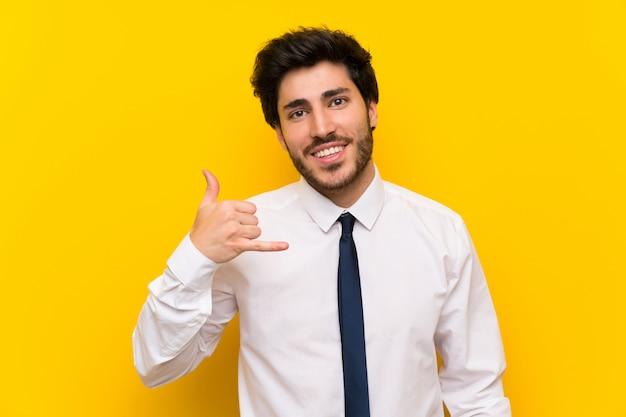 Uomo d'affari sul gesto di fabbricazione giallo isolato del telefono