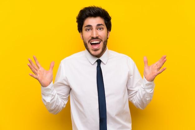 Uomo d'affari sul giallo isolato con espressione facciale a sorpresa