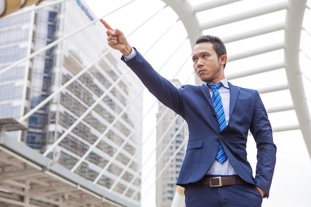 Uomo d'affari sul serio e alzando il pugno con il numero 1 in aria, successo aziendale