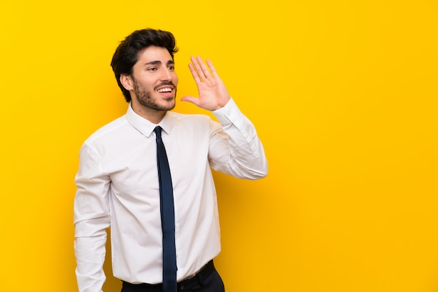 Uomo d'affari sulla parete gialla isolata che grida con la bocca spalancata