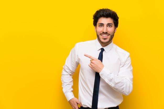 Uomo d'affari sulla parete gialla isolata che indica dito il lato