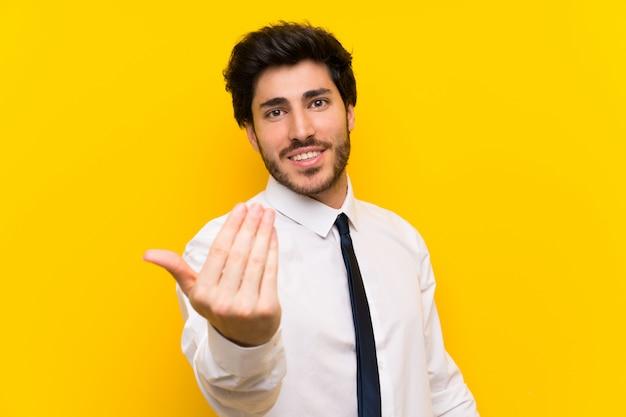 Uomo d'affari sulla parete gialla isolata che invita a venire