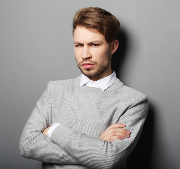 Uomo d'affari triste sopra fondo grigio