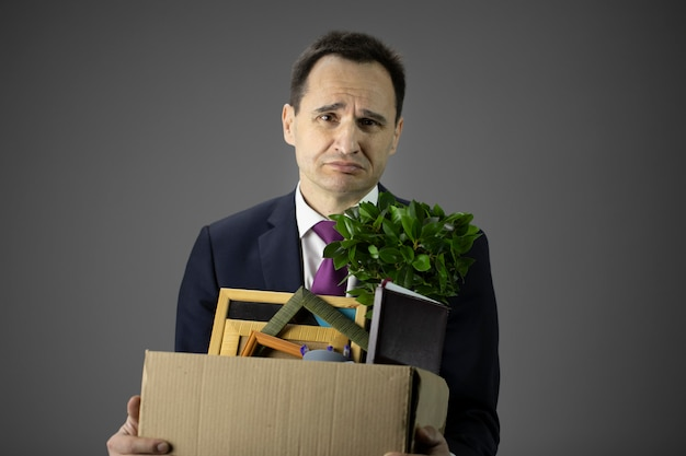 Uomo d'affari turbato con la compagnia vicina della scatola di trasporto, problemi di finanza, insolvenza