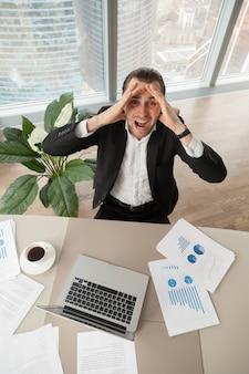 Uomo d'affari turbato sul lavoro che osserva in su