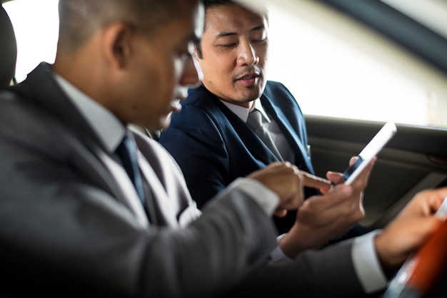 Uomo d'affari usa mobile inside car