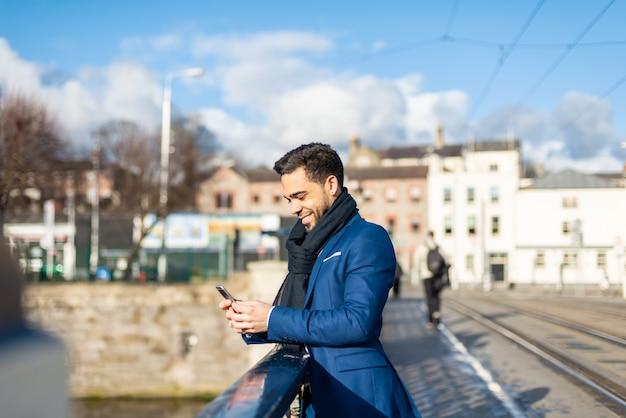 Uomo d'affari utilizzando il telefono cellulare all'aperto.