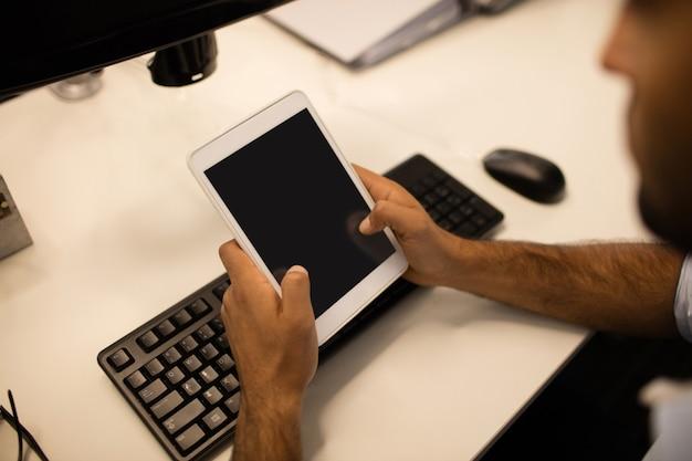 Uomo d'affari utilizzando la tavoletta digitale in ufficio