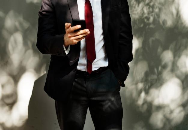 Uomo d'affari utilizzando la tecnologia di comunicazione del telefono cellulare