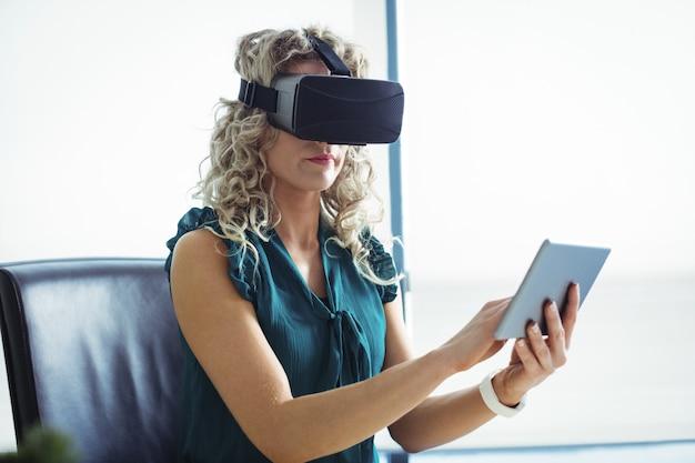 Uomo d'affari utilizzando le cuffie da realtà virtuale e la tavoletta digitale