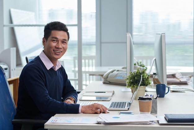 Uomo d'affari vietnamita sorridente che si siede allo scrittorio in ufficio e che esamina macchina fotografica