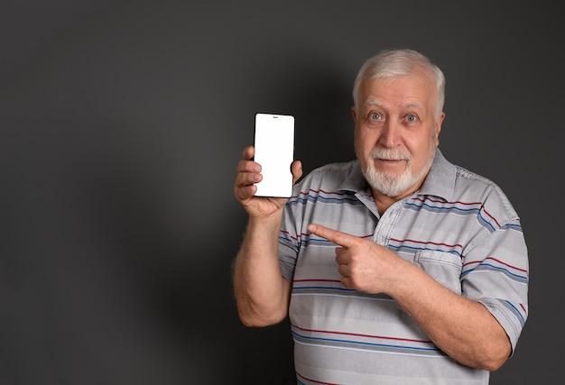 Uomo dai capelli grigi che tiene un telefono e indica il suo dito su gray