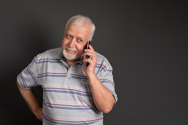 Uomo dai capelli grigi con un telefono sui sorrisi grigi amichevole