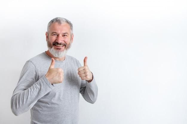 Uomo dai capelli grigi felice adulto con una barba che mostra i pollici in su su una priorità bassa bianca