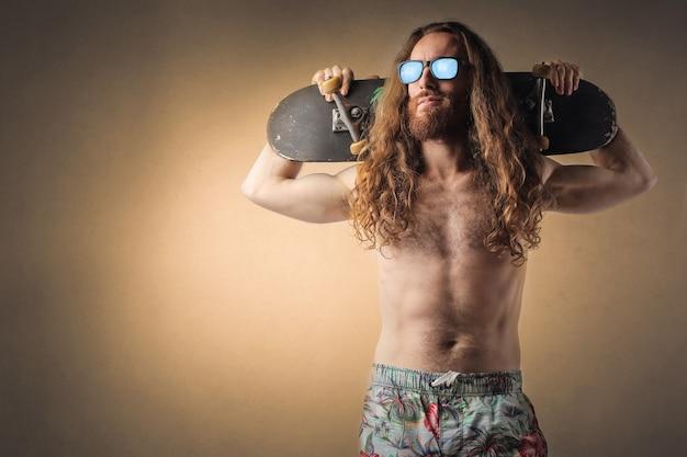 Uomo dai capelli lunghi con skateboard