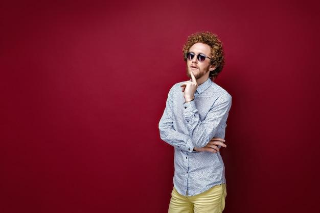 Uomo dai capelli ricci alla moda in occhiali da sole su fondo rosso. thinki