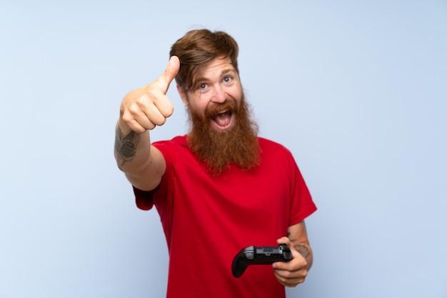 Uomo dai capelli rossi con la barba lunga che gioca con un controller per videogiochi con il pollice in alto perché è successo qualcosa di buono